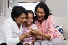 Famiglia di diverse generazioni felice facendo uso del telefono cellulare mentre sedendosi insieme Fotografia Stock Libera da Diritti