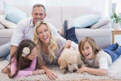 Famiglia di Laughting con il loro giallo labrador dell'animale domestico sulla coperta fotografia stock libera da diritti