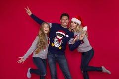 Famiglia di Natale! Mamma felice, papà e piccola figlia sul riposarsi dei cappelli di Santa Claus Abbracci di amore di Enjoyng, l fotografie stock
