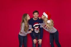 Famiglia di Natale! Mamma felice, papà e piccola figlia sul riposarsi dei cappelli di Santa Claus Abbracci di amore di Enjoyng, l fotografie stock libere da diritti