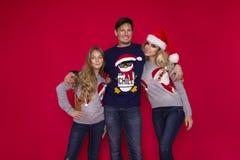 Famiglia di Natale! Mamma felice, papà e piccola figlia sul riposarsi dei cappelli di Santa Claus Abbracci di amore di Enjoyng, l fotografia stock