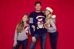 Famiglia di Natale! Mamma felice, papà e piccola figlia sul riposarsi dei cappelli di Santa Claus Abbracci di amore di Enjoyng, l immagine stock