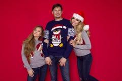 Famiglia di Natale! Mamma felice, papà e piccola figlia sul riposarsi dei cappelli di Santa Claus Abbracci di amore di Enjoyng, l immagini stock libere da diritti