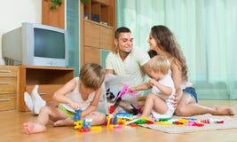 Famiglia di quattro a casa con i giocattoli Fotografie Stock