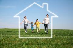 Famiglia di quattro in casa di sogno Fotografie Stock