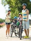 Famiglia di quattro che cicla sulla via fotografia stock