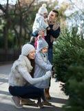 Famiglia di quattro che sceglie X-albero al mercato Immagini Stock Libere da Diritti