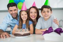 Famiglia di quattro con il dolce ed i regali alla festa di compleanno immagini stock