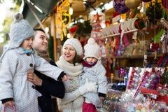 Famiglia di quattro felice al mercato di Natale fotografia stock libera da diritti