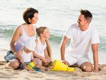 Famiglia di quattro felice alla spiaggia Immagine Stock