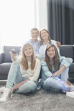 Famiglia di quattro felice che guarda insieme TV a casa Fotografia Stock Libera da Diritti