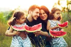 Famiglia di quattro positiva allegra che ha un picnic e che mangia anguria all'aperto in un tempo soleggiato Belle sorelle ricce  Fotografia Stock