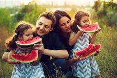 Famiglia di quattro positiva allegra che ha un picnic e che mangia anguria all'aperto in un tempo soleggiato Belle sorelle ricce  Fotografie Stock