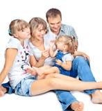 Famiglia di quattro positiva che si siede e che comunica Fotografia Stock Libera da Diritti