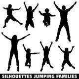 Famiglia di salto felice della siluetta Fotografia Stock
