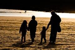 Famiglia di Sillhouetted sulla spiaggia Fotografia Stock