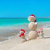 Famiglia di Snowmans alla spiaggia del mare in cappello di Santa Immagini Stock