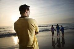 Famiglia di sorveglianza dell'uomo alla spiaggia Fotografie Stock Libere da Diritti