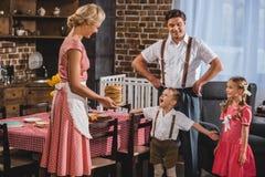 famiglia di stile degli anni 50 che mangia i pancake deliziosi immagine stock