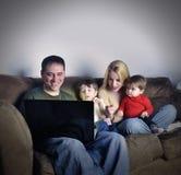 Famiglia di tecnologia a casa sul computer portatile Fotografia Stock Libera da Diritti