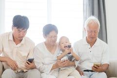 Famiglia dipendente di Smartphone Fotografia Stock