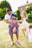 Famiglia divertendosi gioco nel giardino Immagine Stock