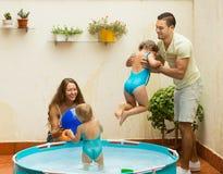 Famiglia divertendosi nello stagno dei bambini fotografia stock libera da diritti