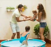 Famiglia divertendosi nello stagno dei bambini Immagine Stock Libera da Diritti