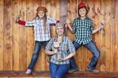 Famiglia divertendosi ridipingendo la tettoia di legno Immagini Stock