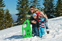 Famiglia divertendosi sulla neve fresca all'inverno Fotografia Stock