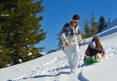 Famiglia divertendosi sulla neve fresca alla vacanza di inverno Immagini Stock