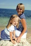 Famiglia divertendosi sulla spiaggia, sulla madre e sulla figlia in mare immagini stock