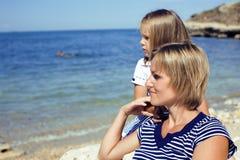 Famiglia divertendosi sulla spiaggia, sulla madre e sulla figlia in mare immagini stock libere da diritti