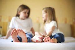 Famiglia dolce a letto Tre sorelle, fine su sui piedi Fotografia Stock