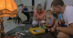Famiglia e bambino che giocano con il giocattolo della costruzione stock footage