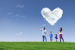 Famiglia e nuvola felici di amore in sosta