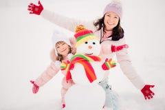 Famiglia e pupazzo di neve nel parco di inverno Fotografie Stock Libere da Diritti