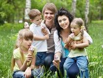 Famiglia esterna con i bambini su erba verde. Immagini Stock Libere da Diritti