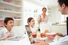 Famiglia facendo uso dei dispositivi di Digital alla Tabella di prima colazione Immagine Stock