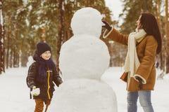 Famiglia felice in abbigliamento caldo Madre e figlio sorridenti che rendono un pupazzo di neve all'aperto Il concetto delle atti Fotografia Stock