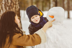Famiglia felice in abbigliamento caldo Madre e figlio sorridenti che rendono un pupazzo di neve all'aperto Il concetto delle atti Immagine Stock Libera da Diritti