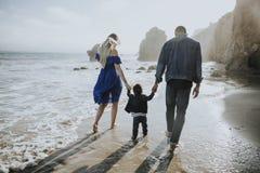 Famiglia felice ad una spiaggia immagini stock