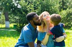 Famiglia felice afroamericana: padre, mamma e neonato neri sulla natura Usilo per un bambino, parenting Fotografie Stock