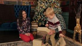 Famiglia felice ai regali di apertura di natale insieme archivi video