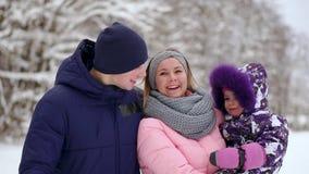 Famiglia felice al tramonto Il padre, la madre e due figlie dei bambini sono divertentesi e giocanti sulla passeggiata nevosa del archivi video