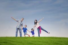 Famiglia felice alla collina verde Immagine Stock