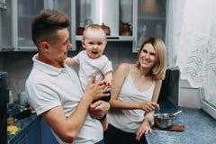 Famiglia felice alla cucina Giovani genitori che alimentano il loro da adorabile immagini stock libere da diritti