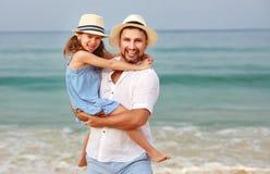 Famiglia felice alla spiaggia abbraccio della figlia del bambino e del padre in mare fotografia stock libera da diritti