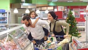 Famiglia felice allegra fare gli acquisti nel deposito per le feste di Natale video d archivio