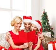 Famiglia felice in cappelli di Santa con la cartolina d'auguri Fotografia Stock
